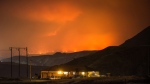A wildfire burns on a mountain in the distance east of Cache Creek behind a house in Boston Flats, B.C., in the early morning hours of Monday July 10, 2017. THE CANADIAN PRESS/Darryl Dyck