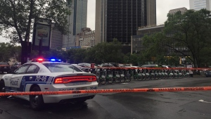 Montreal police stand guard near Victoria Square as a man made threats on Friday, July 14, 2017 (Angela Mackenzie/CTV Montreal)
