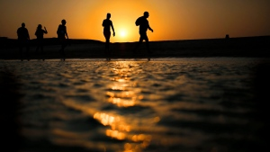 In this file picture taken Thursday, Aug. 20, 2015, tourists walk on the Giftun Island beach as the sun sets over the Red Sea in Hurghada, Egypt. (Hassan Ammar/AP)