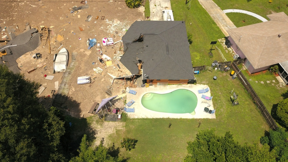In this aerial photo, debris is strewn about after a sinkhole damaged two homes in Land O' Lakes, Fla. on Friday, July 14, 2017. (Luis Santana/Tampa Bay Times via AP)