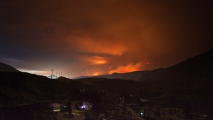 A wildfire burns on a mountain in the distance east of Cache Creek behind a trailer park that was almost completely destroyed by wildfire, in Boston Flats, B.C., in the early morning hours of Monday July 10, 2017. (Darryl Dyck/The Canadian Press)