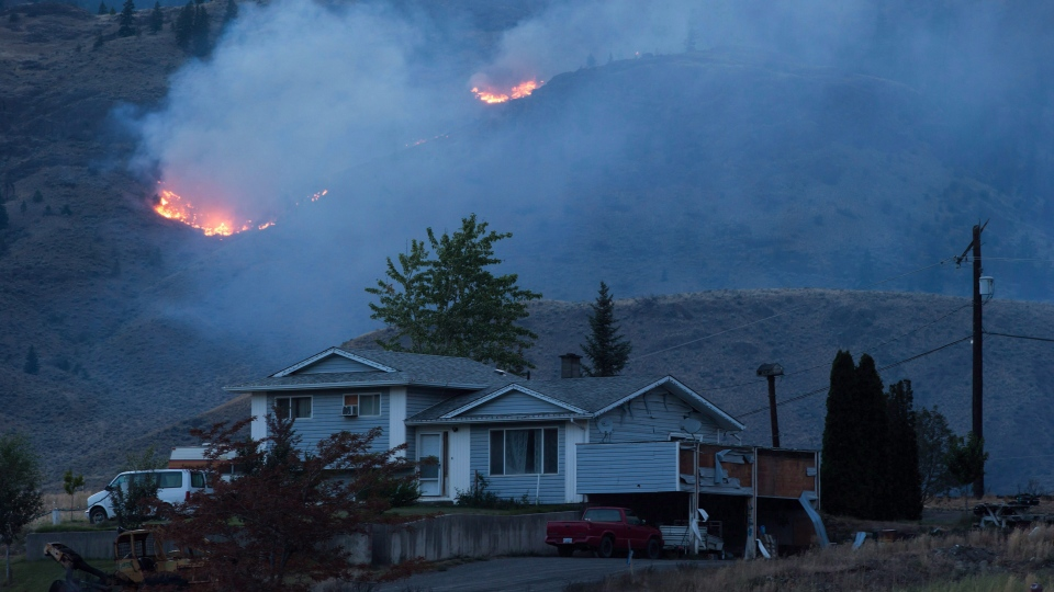 A wildfire burns on a mountain in the distance behind a house that remains standing on the Ashcroft First Nation, near Ashcroft, B.C., late Sunday July 9, 2017. (THE CANADIAN PRESS / Darryl Dyck)