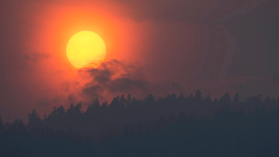 Smoke is seen rising in front of the sun as a wildfire burns near Little Fort, B.C. Tuesday, July 11, 2017. THE CANADIAN PRESS/Jonathan Hayward