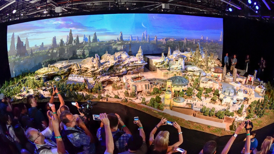 "Members of the media get their first look at a 50-foot, detailed model of ""Star Wars"" land during a media preview for Disney's D23 Expo in Anaheim, Calf., on Thursday, July 13, 2017. (Jeff Gritchen/The Orange County Register via AP)"