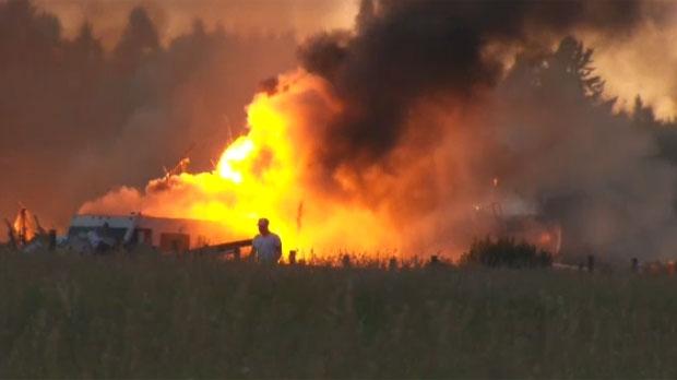 A man walks through a field near Saturday night's building fire in Priddis