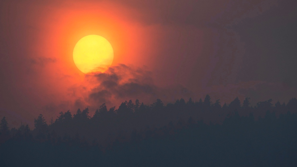 In this file photo, smoke is seen rising in front of the sun as a wild fire burns near Little Fort, B.C. Tuesday, July 11, 2017. (Jonathan Hayward / THE CANADIAN PRESS)