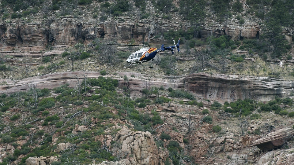 A helicopter flies above the rugged terrain along the banks of the East Verde River during a search and rescue operation for victims of a flash flood in Payson, Ariz. on Sunday, July 16, 2017. (AP / Ralph Freso)