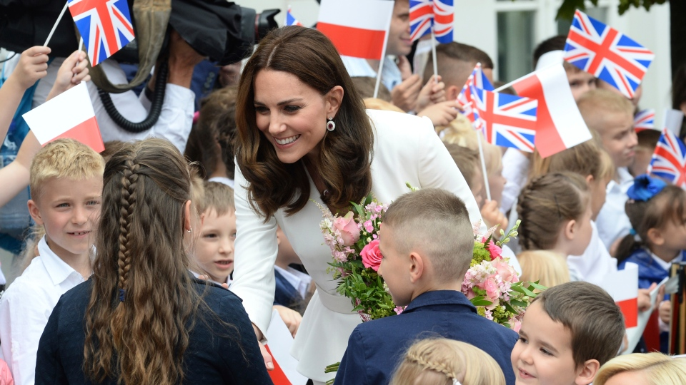 Children welcome Kate, the Duchess of Cambridge, during her visit with Prince William in front of the presidential palace, in Warsaw, Poland, Monday, July 17, 2017. (AP Photo/Alik Keplicz)
