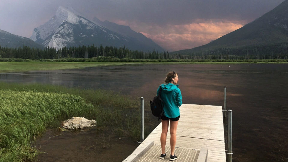 A woman takes in the smoke blanketing Mt. Rundle from a forest fire in Kootenay National park as she stands on a dock on the Vermillion lakes near Banff, Alta. July 15, 2017. (Adrian Wyld/THE CANADIAN PRESS)