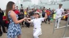 Sub-lieutenant Tristan Lapointe reacts after Gabrielle Lambert accepts his marriage proposal as Rear Admiral John Newton, right, head of Canada's East Coast navy, looks on as HMCS St. John's returns to Halifax on Monday, July 17, 2017. (Andrew Vaughan / THE CANADIAN PRESS)