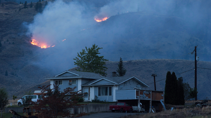 A wildfire burns on a mountain in the distance behind a house that remains standing on the Ashcroft First Nation, near Ashcroft, B.C., late Sunday July 9, 2017. (THE CANADIAN PRESS/Darryl Dyck)