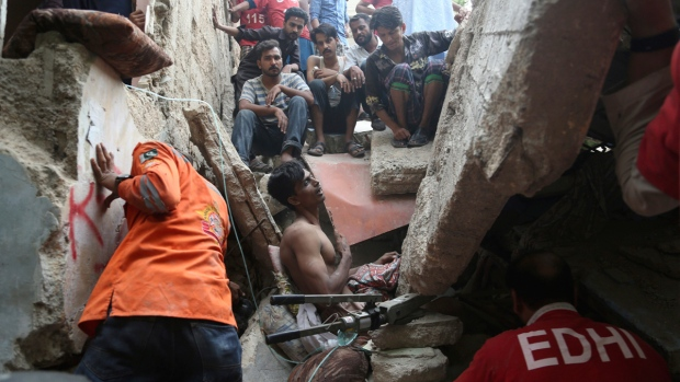 Pakistani volunteers try to rescue a trapped resident in Karachi, Pakistan, on July 18, 2017. (Shakil Adil / AP)