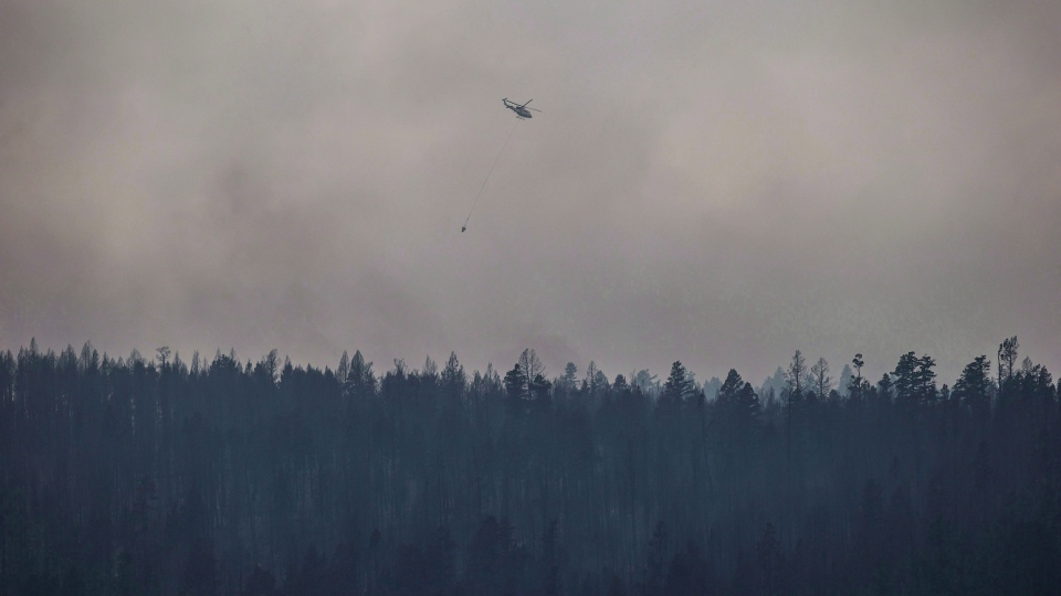A helicopter is used to battle a wildfire burning on the top of a mountain near Ashcroft, B.C., on Monday, July 10, 2017. Environment Canada says smoke from British Columbia's wildfires will likely result in high-risk air quality levels in parts of central Alberta by Wednesday. THE CANADIAN PRESS/Darryl Dyck