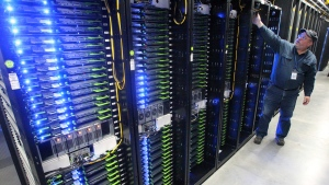 Chuck Goolsbee, site director,, shows the computer servers that store users' photos and other data, at the Facebook site in Prineville, Ore. in this Oct. 15, 2013 file photo. (Andy Tullis/The Bulletin, via AP, File)