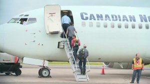 Quebec City firefighters board a plane heading to Kamloops, B.C. on July 18, 2017