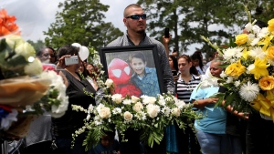 Flowers and a photo of Josue Flores to be placed at his grave site are held by an unidentified man during a funeral service at Historic Hollywood Cemetery, Tuesday, May 24, 2016, in Houston. (Gary Coronado / Houston Chronicle via AP)