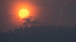 Smoke is seen rising in front of the sun as a wild fire burns near Little Fort, B.C., on July 11, 2017. THE CANADIAN PRESS/Jonathan Hayward