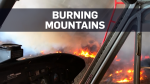Helicopter footage of mountains up in flames