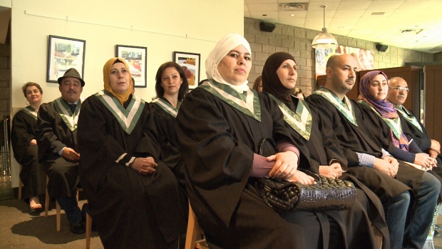 Syrian refugees wait to accept their certificates.
