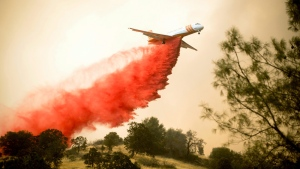 An air tanker drops retardant while battling a wildfire fire near Mariposa, Calif., on Wednesday, July 19, 2017. (AP /Noah Berger)