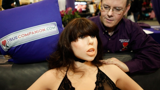 Douglas Hines, founder of True Companion, poses with a life-size rubber doll named Roxxxy during the Adult Entertainment Expo in Las Vegas, Saturday, Jan. 9, 2010. (AP /Paul Sakuma)