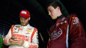 Alex Bowman, right, watches as Dale Earnhardt Jr. sends out a tweet while waiting under a tunnel for driver introductions to begin before a NASCAR Sprint Cup Series auto race at the Daytona International Speedway, in Daytona Beach, Fla. on July 5, 2014.