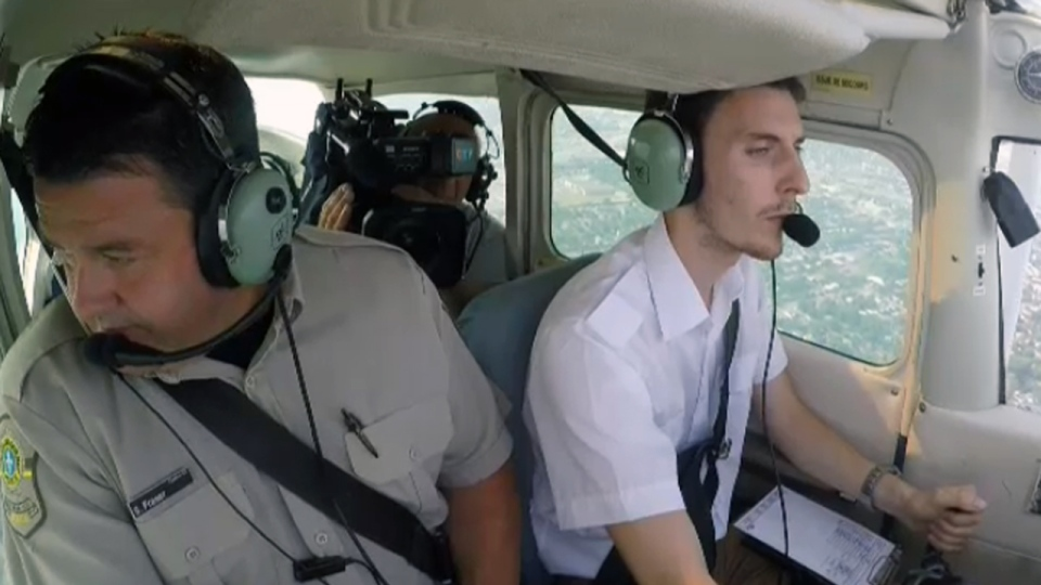 An SQ officer looks out a plane window for drivers breaking the law (July 20, 2017)