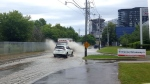 Cars are seen driving through severe flooding on Bayview Avenue.