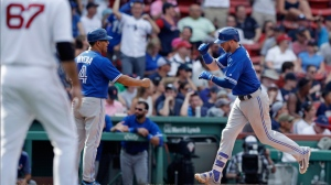 Toronto Blue Jays' Justin Smoak, right, is congratulated by third base coach Luis Rivera (4) after hitting a solo home run off Boston Red Sox relief pitcher Brandon Workman (67) during the ninth inning of a baseball game at Fenway Park in Boston, Thursday, July 20, 2017. (AP Photo/Charles Krupa)