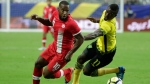 Canada's David Junior Hoilett, left, is chased by Jamaica's Cory Burke during a CONCACAF Gold Cup quarterfinal soccer match, in Glendale, Ariz., on Thursday, July 20, 2017. (AP Photo/Matt York)