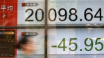 A woman walks past an electronic stock board showing Japan's Nikkei 225 index at a securities firm in Tokyo on Friday, July 21, 2017. (AP / Eugene Hoshiko)