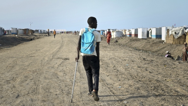 Former child soldier James walks down the road from his small hut in a protection of civilians site to his first day at his new school, after recently being reunited with his mother who had thought he was dead, in Bentiu, South Sudan on Monday, May 29, 2017. (AP / Sam Mednick)