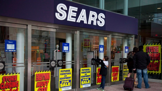 """People wait for Sears to open in downtown Vancouver, Friday, September 21, 2012. Sears Canada (TSX:SCC) announced Thursday it is laying off 700 workers across the country as part of a move to """"right-size"""" the company and focus on restructuring its business. (THE CANADIAN PRESS/Jonathan Hayward)"""