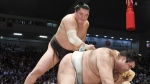 Mongolian grand champion Hakuho, left, topples champion Takayasu at the Nagoya Grand Sumo Tournament in Nagoya, Japan, on July 21, 2017. (Yoshiaki Sakamoto/Kyodo News)
