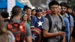 Peter Barrera wears a Captain America costume as he waits in line during the first day of Comic-Con Thursday, July 20, 2017, in San Diego. Comic-Con, which started as a comic-book convention with 300 participants in 1970 and has grown into a corporate-heavy media showcase that draws more than 130,000 attendees, runs through Sunday in San Diego. (AP Photo/Gregory Bull)
