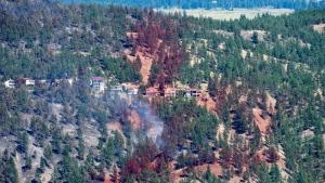 Smoke and fire retardant are seen along a neighbourhood in Lake Country, B.C., Sunday, July 16, 2017.  THE CANADIAN PRESS/Jonathan Hayward