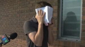 Stelianos Psaroudakis covers his face and neck wounds while leaving the Cochrane RCMP detachment on the evening of July 21