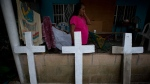 In this July 1, 2017 file photo, Isabel Osorio Luna, the great-grandmother of the murdered Martinez children, walks past homemade concrete crosses being painted to adorn the simple tombs of the family of six, in Coatzacoalcos, Veracruz State, Mexico. (AP Photo/Rebecca Blackwell, File)