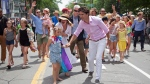 Sophie Gregoire Trudeau and her husband, Canadian Prime Minister Justin Trudeau, react to a little girl who came up to say, hello, as they take part in the annual Halifax Pride Parade on Saturday, July 22, 2017. (THE CANADIAN PRESS / Stringer)
