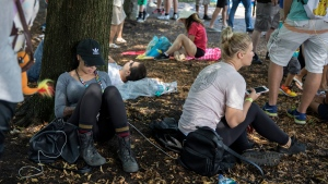 Festival goers sit in the shade at the Pokemon Go Fest Saturday, July 22, 2017, at Grant Park in Chicago. (Erin Hooley / Chicago Tribune via AP)