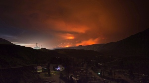 A wildfire burns on a mountain in the distance east of Cache Creek behind a trailer park that was almost completely destroyed by wildfire, in Boston Flats, B.C., in the early morning hours of July 10, 2017. (THE CANADIAN PRESS / Darryl Dyck)