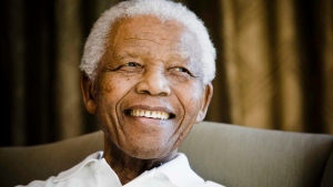 Former South African President Nelson Mandela smiles during a meeting with a group of American and South African students in Johannesburg, South Africa. (AP Photo/Theana Calitz-Bilt, Pool, File)