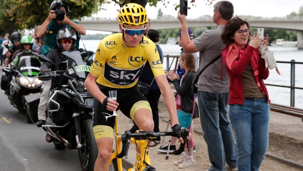 Chris Froome, wearing the overall leader's yellow jersey, holds a cup of Champagne during the twenty-first and last stage of the Tour de France cycling race over 103 kilometers (64 miles) with start in Montgeron and finish in Paris, France, Sunday, July 23, 2017. (Benoit Tessier, Pool via AP)