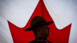 An RCMP officer is silhouetted against a Canadian flag during a special Canada Day citizenship ceremony in West Vancouver, B.C., on Saturday, July 1, 2017. (THE CANADIAN PRESS/Darryl Dyck)