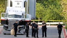 San Antonio police officers investigate the scene Sunday, July 23, 2017, where eight people were found dead in a tractor-trailer loaded with at least 30 others outside a Walmart store in stifling summer heat in what police are calling a horrific human trafficking case, in San Antonio. (AP Photo/Eric Gay)