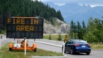 A sign warns of a forest fire in the area as smoke haze from forest fires burning in Alberta and British Columbia hangs over Banff, Alta., in Banff National Park, Friday, July 21, 2017. THE CANADIAN PRESS/Jeff McIntosh