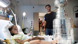 Pittsburgh Penguins' Kris Letang shows off the Stanley Cup to Roya Boudjemaa during a visit to Sainte Justine hospital for sick children in Montreal, Sunday, July 23, 2017. THE CANADIAN PRESS/Graham Hughes