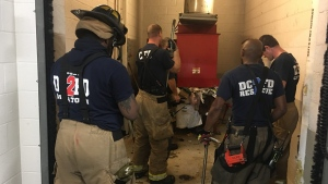 In this photo provided by DC Fire and EMS, emergency personnel respond to a call from a man who was stuck in a trash chute, early Sunday, July 23, 2017, in Washington. (Vito Maggiolo/DC Fire and EMS Department via AP)