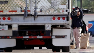 Evidence is collected at the scene where eight people were found dead in a tractor-trailer loaded with multiple others, outside a Walmart store in stifling summer heat in what police are calling a horrific human trafficking case, Sunday, July 23, 2017, in San Antonio. (AP Photo/Eric Gay)