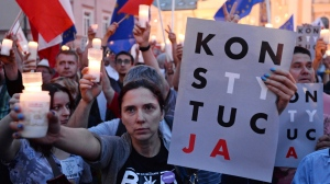"""Anti-government protesters raise candles and placards reading """"Constitution"""", as they gather in front of the Supreme Court in Warsaw, Poland, Sunday, July 23, 2017. Protests continue across Poland over plans by the populist ruling party Law and Justice to put the Supreme Court and the rest of the judicial system under the party's political control. (AP Photo/Alik Keplicz)"""